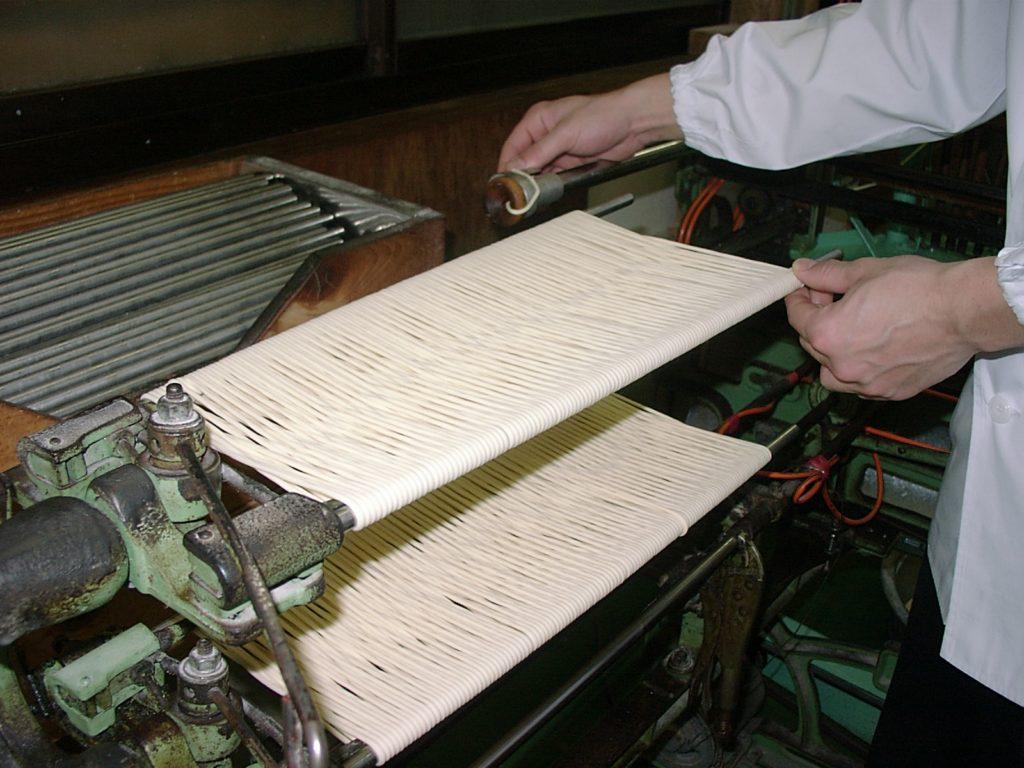 島原手延素麺協同組合_熟成させた麺に「より」を掛けながら、2本の棒に「8の字」状態に掛けます